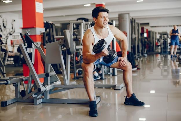 Een jonge en atletische jongen houdt zich bezig met sporten in de sportschool