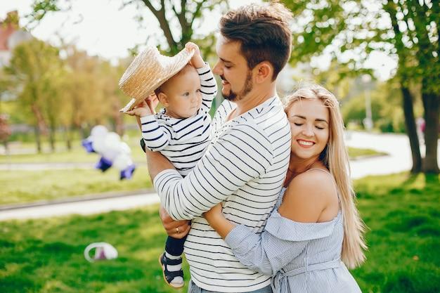 Een jonge en mooie blonde moeder in een blauwe jurk, samen met haar knappe man