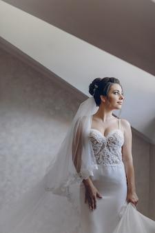 Een jonge en mooie bruid die thuis zich dichtbij venster bevindt