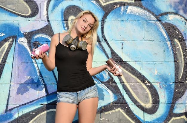 Een jonge en mooie sexy graffitikunstenaar met een verfspray