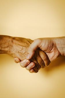 Een jonge en witte hand schudt een oude en zwarte hand
