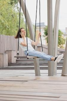 Een jonge en zelfverzekerde vrouwelijke blogger of marketeer praat aan de telefoon en rijdt op een schommel