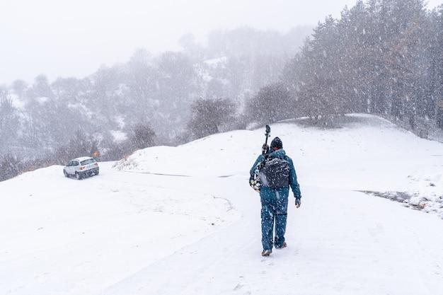 Een jonge fotograaf die in de berg aizkorri van gipuzkoa loopt. besneeuwde landschap door wintersneeuw
