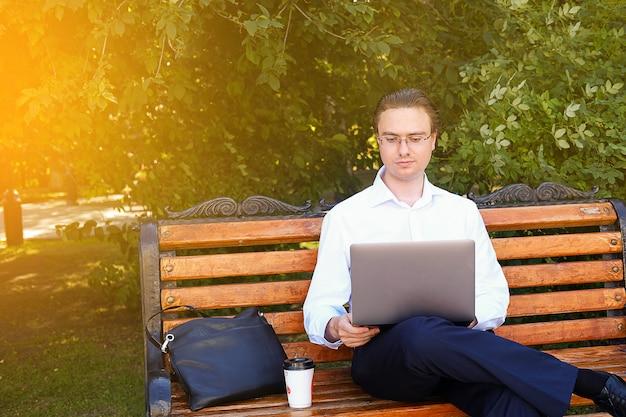 Een jonge freelancer in een wit shirt en een bril werkt in het park.