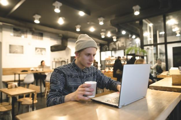 Een jonge freelancer werkt voor een laptop in een gezellig café voor een kopje koffie. de student gebruikt internet in een café