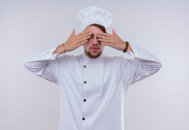 Een jonge, gebaarde chef-kokmens die witte eenvormige fornuis en hoed draagt die zijn ogen behandelt met handen op een witte muur Gratis Foto