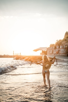 Een jonge gebruinde vrouw in een mooi zwempak met een strohoed staat en rust op een tropisch strand met zand en kijkt naar de zonsondergang en de zee. selectieve aandacht. vakantieconcept aan zee