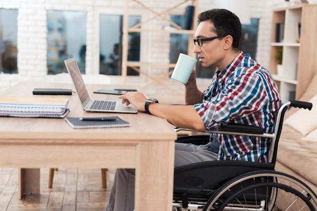 Een jonge gehandicapte man werkt thuis met een laptop