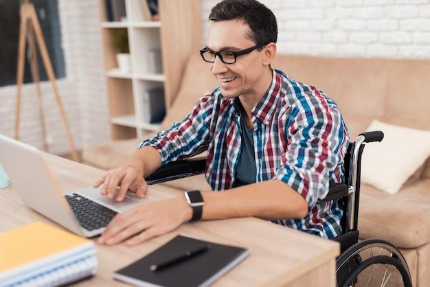 Een jonge gehandicapte man werkt thuis.