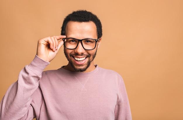 Een jonge gelukkig lachend grappig mannetje geïsoleerd tegen beige.