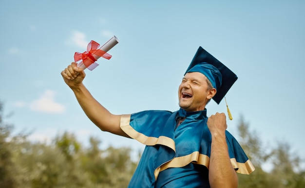 Een jonge gelukkig lachende man viert zijn diploma en phd-diploma over blauwe hemel. afstuderen concept vieren