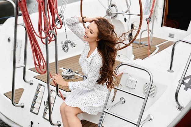 Een jonge gelukkig vrouw met lang mooi haar in witte jurk poseren op het dek van een jachtschip