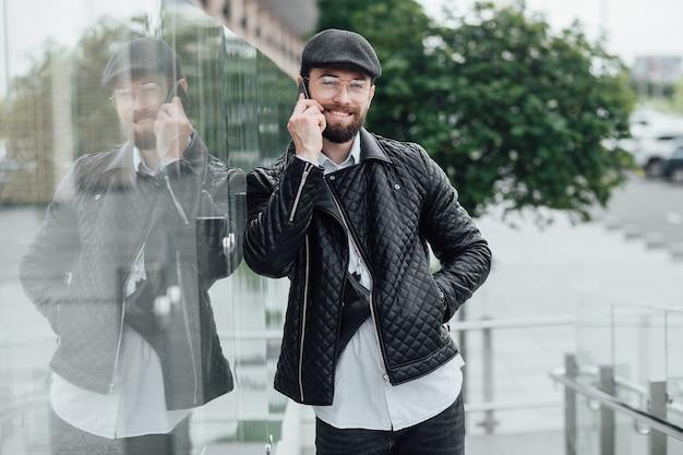 Een jonge, gelukkige, knappe, stijlvolle man spreekt via de mobiele telefoon in de straten van de stad