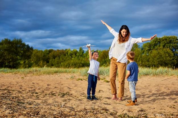 Een jonge gelukkige moeder met twee jongens die op het zand in de buurt van het bos spelen, in handen van een van hen een model van een civiel vliegtuig en een hoed op zijn hoofd
