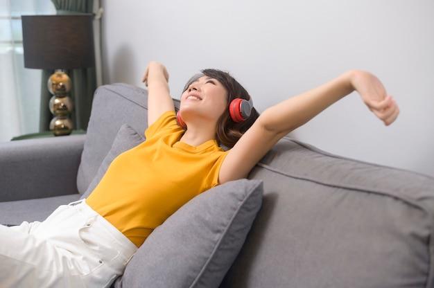 Een jonge gelukkige vrouw die naar muziek luistert en thuis ontspant