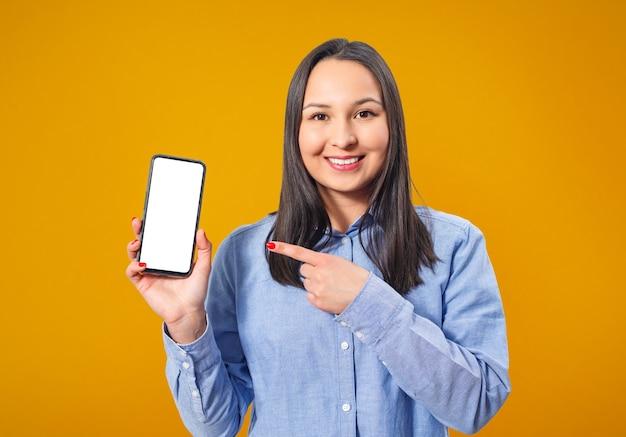 Een jonge, gelukkige vrouw houdt een smartphone vast en wijst naar een leeg wit scherm. op een gele achtergrond.