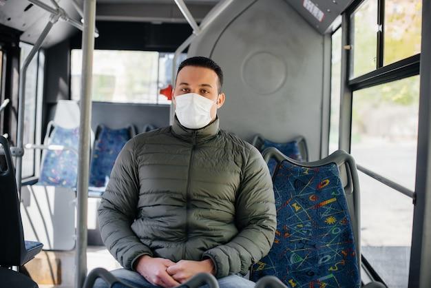 Een jonge gemaskerde man maakt alleen gebruik van het openbaar vervoer tijdens een pandemie. bescherming en preventie covid 19.