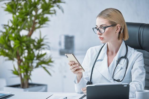 Een jonge gespecialiseerde arts werkt aan een bureau in zijn kantoor en stuurt berichten naar zijn telefoon