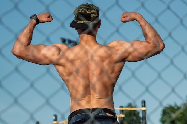 Een jonge gespierde man met een blote romp rust na de training, een atleet