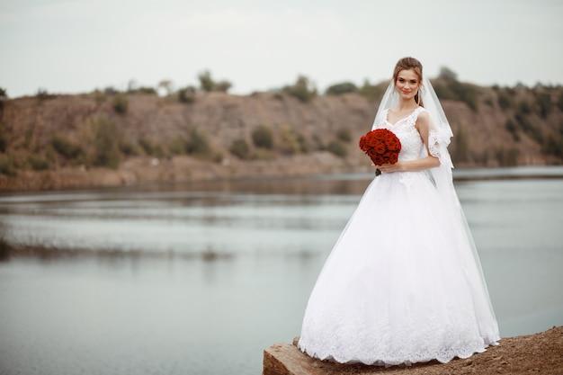 Een jonge glimlachende en mooie bruid in een witte jurk staat