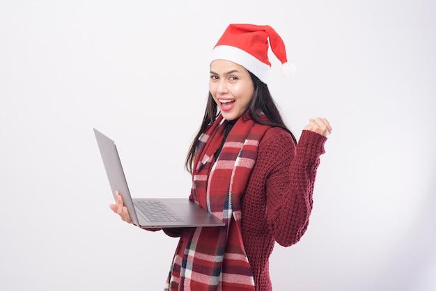 Een jonge glimlachende vrouw die de rode hoed van de kerstman draagt die videogesprek op sociaal netwerk maakt