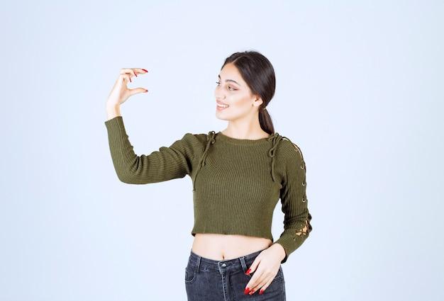 Een jonge glimlachende vrouw die met handen gebarend die groot en groot formaatteken tonen.