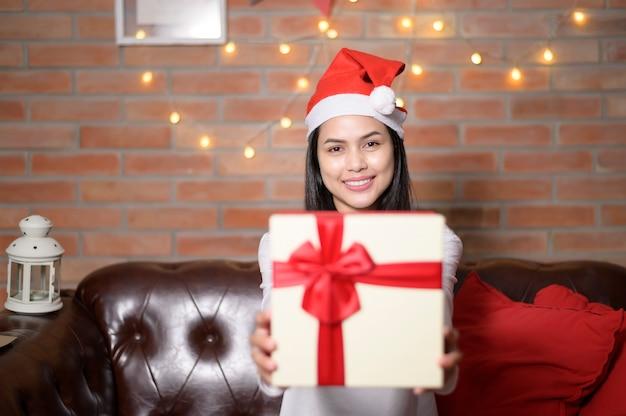 Een jonge glimlachende vrouw die rode kerstmanhoed draagt die een giftdoos toont op eerste kerstdag, vakantieconcept.