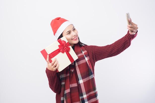 Een jonge glimlachende vrouw die rode kerstmanhoed draagt die een selfie op wit neemt
