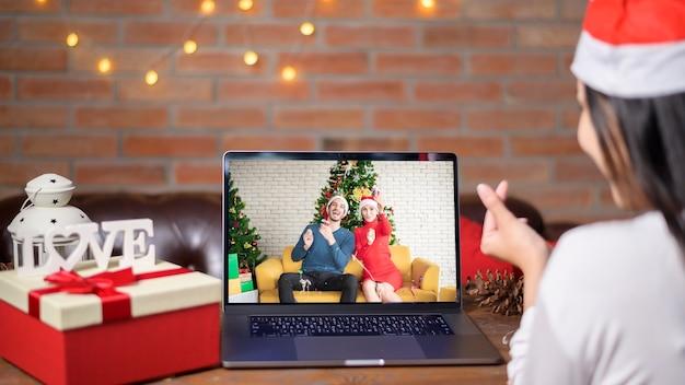Een jonge glimlachende vrouw die rode kerstmanhoed draagt die videogesprek voert op sociaal netwerk met familie en vrienden op eerste kerstdag.