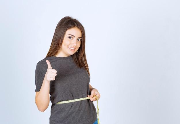 Een jonge glimlachende vrouw die taille meet en een duim toont.