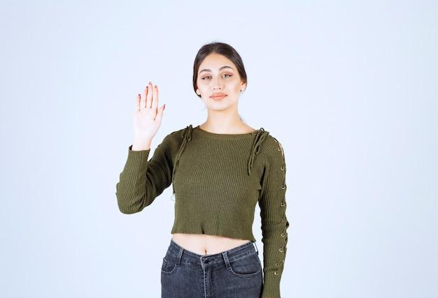 Een jonge glimlachende vrouw in een groene trui die met een hand zwaait.