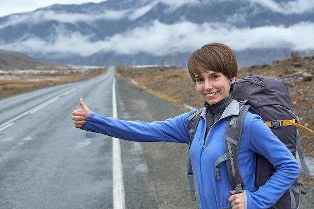 Een jonge glimlachende vrouw reist in de bergen. stopt de auto op de weg (liften), steekt zijn hand op.