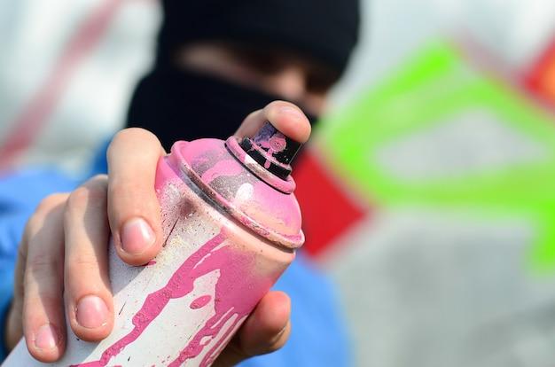 Een jonge graffitikunstenaar in een blauw jasje en een zwart masker houdt