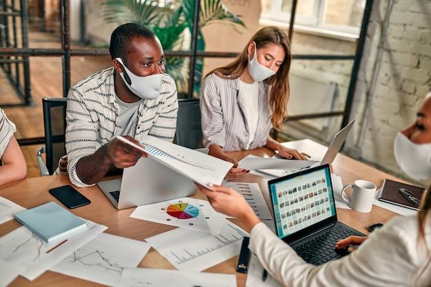 Een jonge groep mensen in beschermende maskers zitten met laptops op kantoor en bespreken.