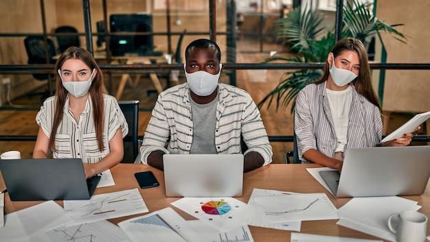 Een jonge groep multi-etnische zakenmensen in beschermende maskers werkt op laptops in een modern kantoor.