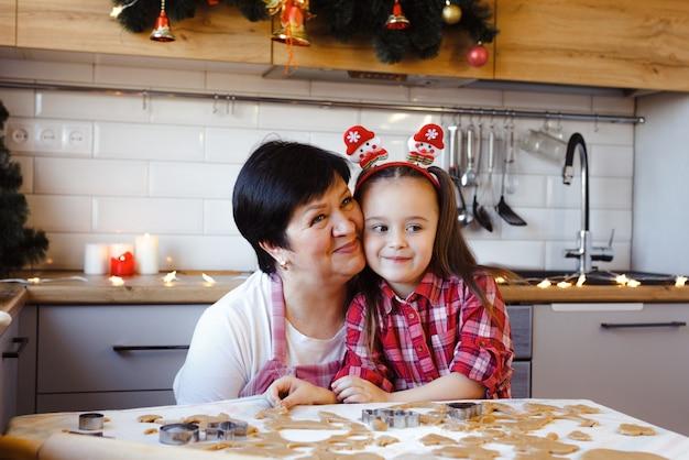 Een jonge grootmoeder en kleindochter omhelzen elkaar in de keuken terwijl ze op kerstavond koekjes bakken.