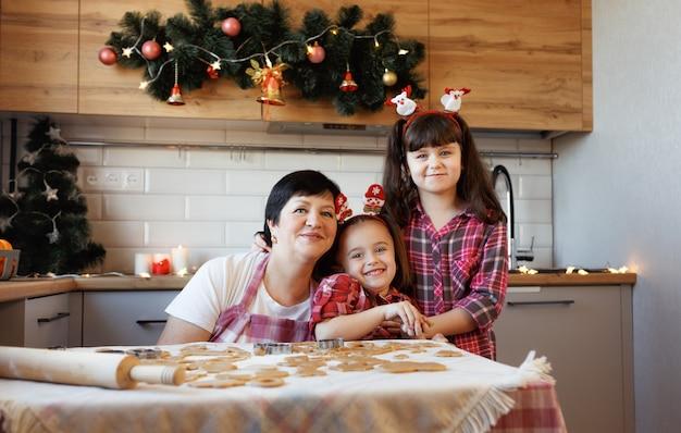 Een jonge grootmoeder met twee kleindochters knuffelen en lachen in de keuken die is ingericht voor de kerstvakantie.