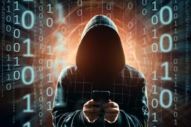 Een jonge hacker in een kap hackt een smartphone, een hacker valt een silhouet van een man aan