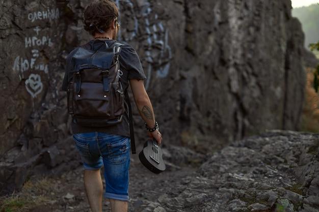 Een jonge hippieman met een leren rugzak loopt in de buurt van de rotsen en houdt een ukelele hoog in zijn hand.