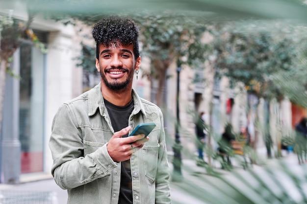 Een jonge hipsanische man die zijn mobiele telefoon buiten gebruikt op een bewolkte dag
