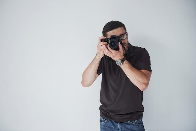 Een jonge hipster man in oculairs houdt een dslr camera in handen staande tegen een witte muur