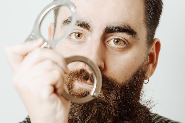 Een jonge hipster man met een witte achtergrond met handboeien en serieus op zoek naar de camera