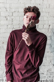Een jonge hipsterjongen die poseert met een droge roos en een rode coltrui draagt