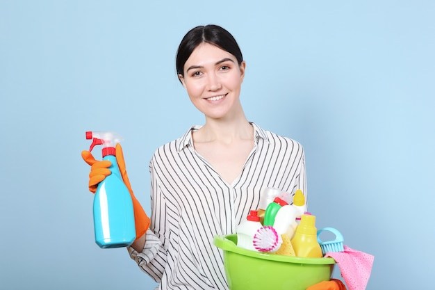 Een jonge huisvrouw houdt schoonmaakproducten in zijn handen op een gekleurde achtergrond