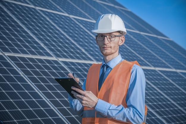 Een jonge ingenieur controleert met tablet een verrichting van zon en netheid op gebied van fotovoltaïsche zonnepanelen op een zonsondergang