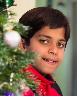 Een jonge jongen die lacht vanuit de kerstboom