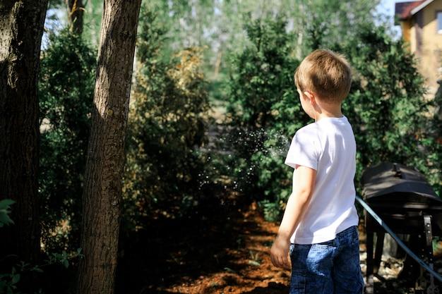 Een jonge jongen die planten en decoratieve kerstbomen in de tuin van zijn huis water geeft.