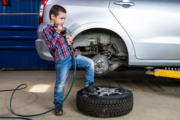 Een jonge jongen, een jonge auto-werker, maakt een bandenwissel met een pneumatische sleutel in de garage van een tankstation. een kind leert het mechanica veranderende beroep in autoreparatiedienst.