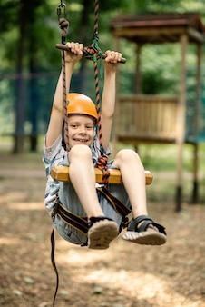Een jonge jongen hangt aan de lijn in het touwpark. sportentertainment voor een kind, actieve rust.