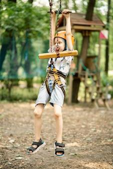 Een jonge jongen in een bergbelay en een teenslipper gaat door een hindernisbaan. actieve, sportieve activiteit in de zomer voor een kind.
